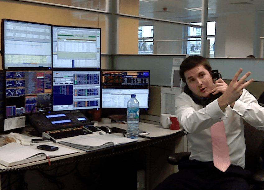Ein Trader vor Bildschirmen als Symbol der bösen Finanzmärkte