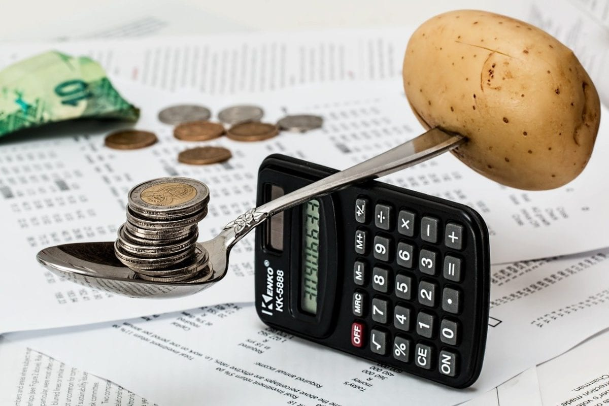 Kartoffel und Geldmünzen auf der Waage der Verbraucherpreise