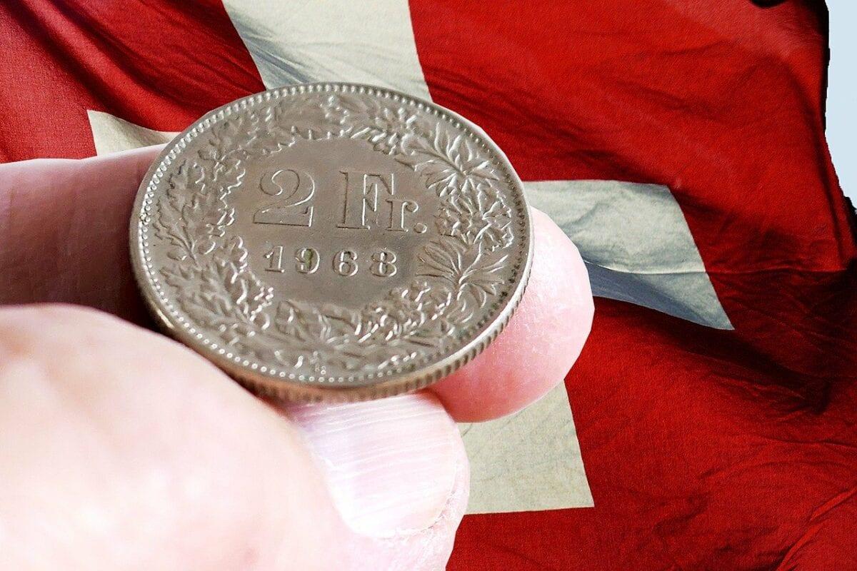 Eine Schweizer Franken Münze vor Schweizer Flagge