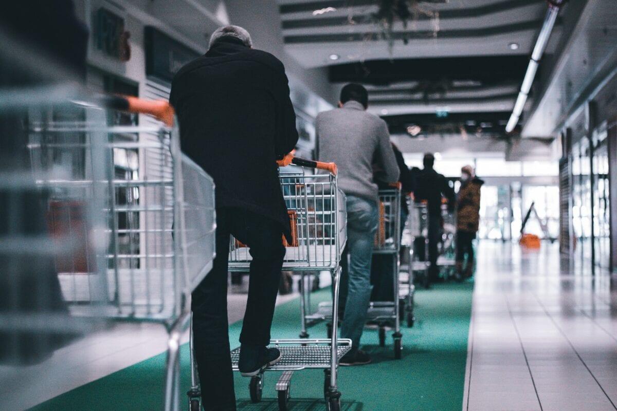 Menschen in Schlange mit Einkaufswagen