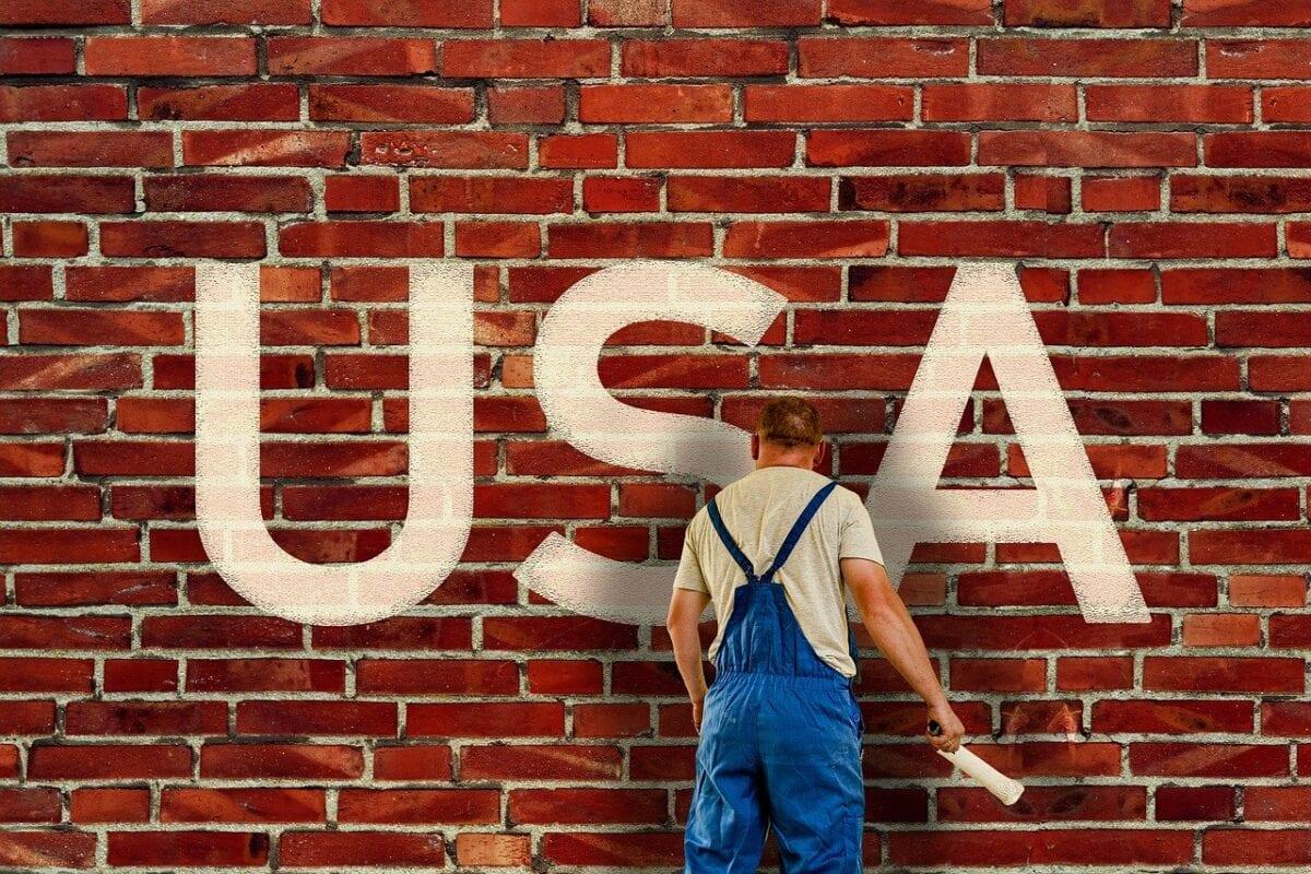 Symbolbild eines Malers vor einer Wand mit den Worten USA