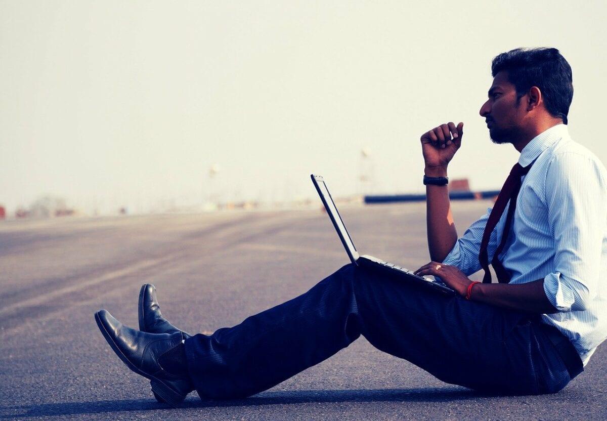 Mann mit Laptop auf Straße