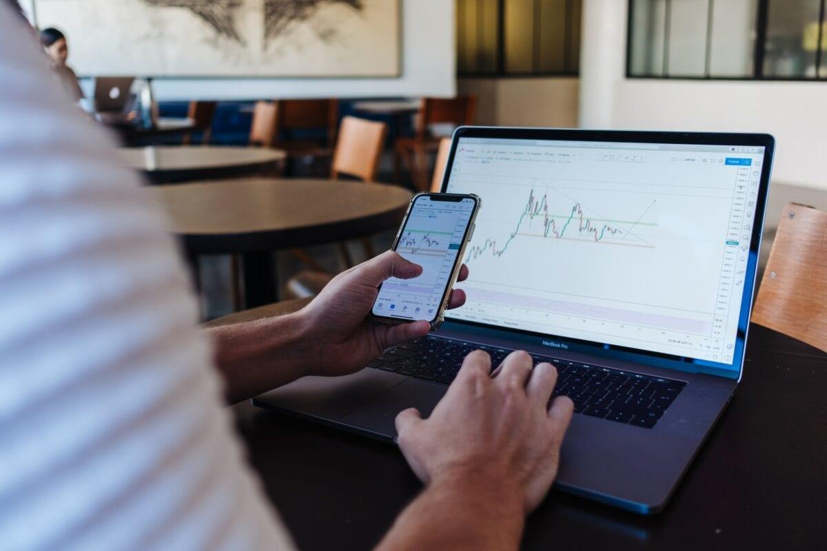 Anleger schaut auf Laptop und Handy