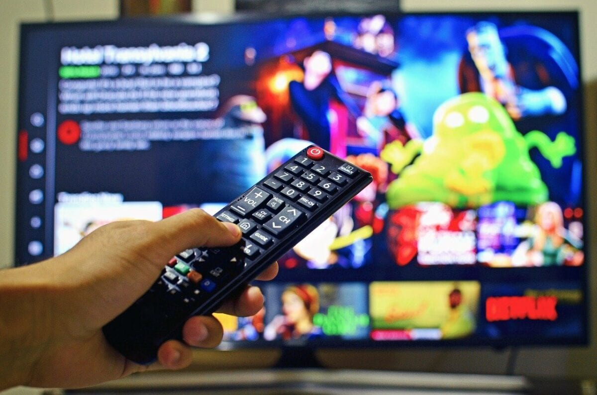 Fernbedienung vor Fernseher mit Netflix-Programm