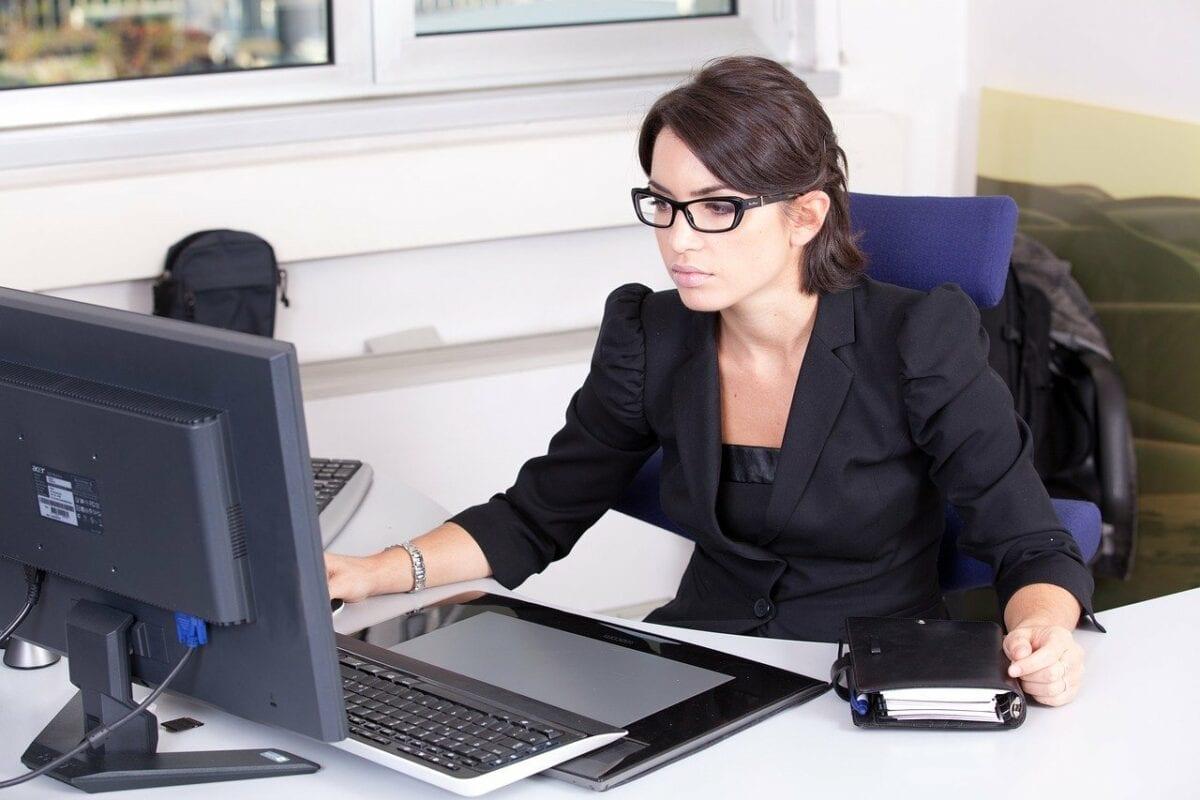 Frau arbeitet im Büro am Computerbildschirm