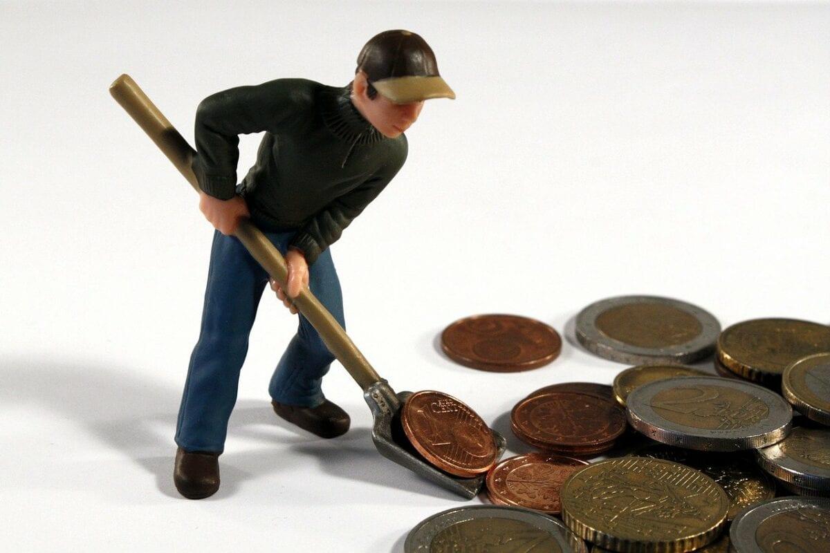 Mann scheffelt Geldmünzen