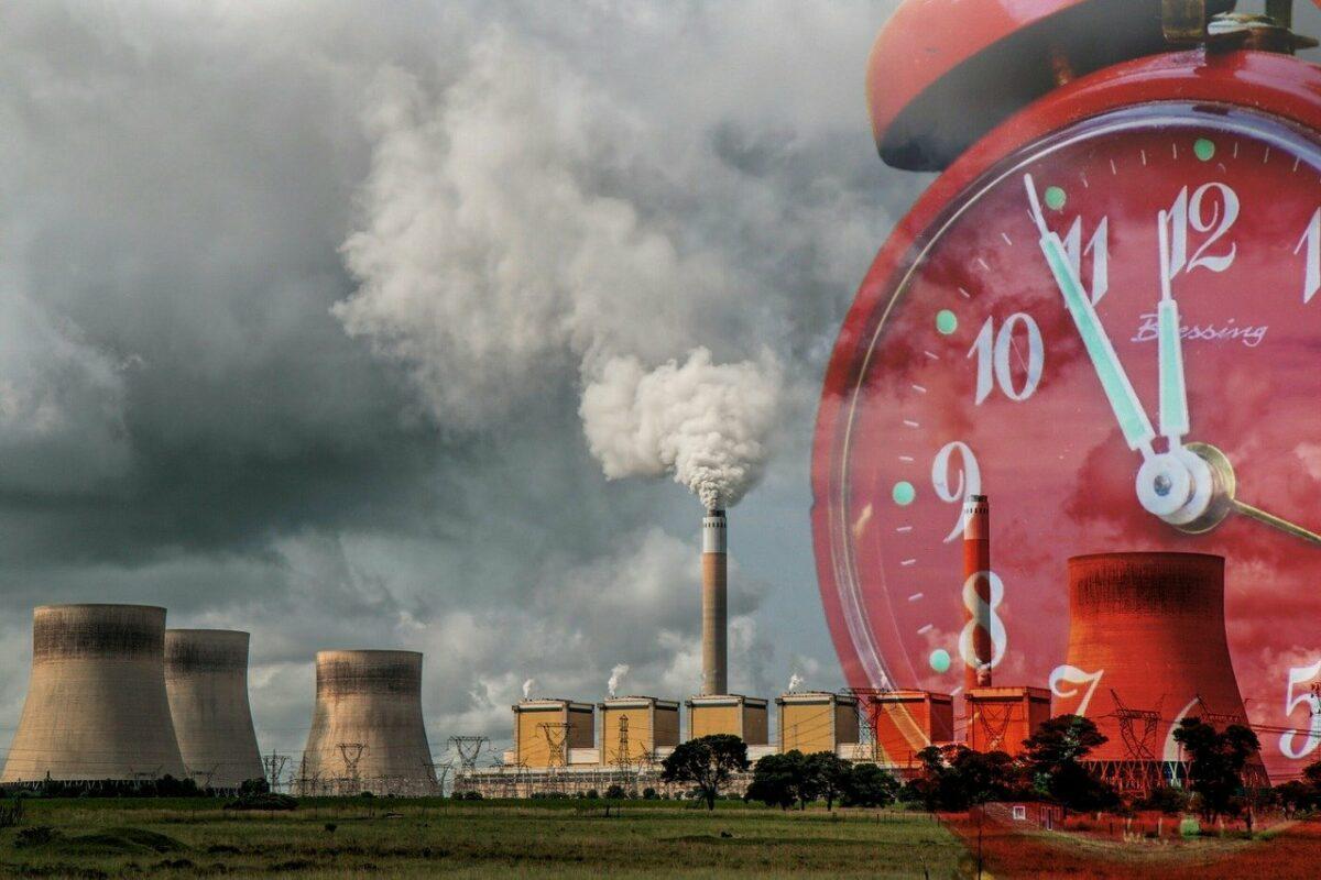 Kohlekraftwerk mit Uhr als symbolisches Bild für die globale Energiekrise